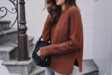 16 ripped grey jeans, a burnt orange sweater and a black bag