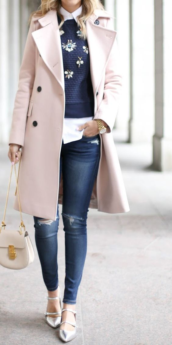 silver shoes, ripped jeans, a white shirt, a navy embellished sweater and a pink coat