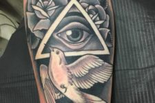 All seeing eye and white dove tattoo on the arm