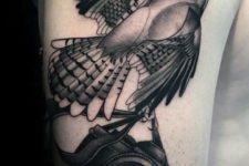 Bird and camera tattoo on the arm