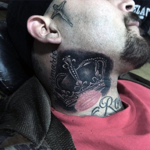 Black and white crown tattoo on the neck