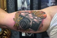 Camera and grape tattoo on the biceps