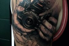 Camera held by hands tattoo on the arm