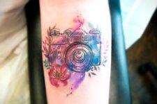 Colorful camera tattoo on the forearm
