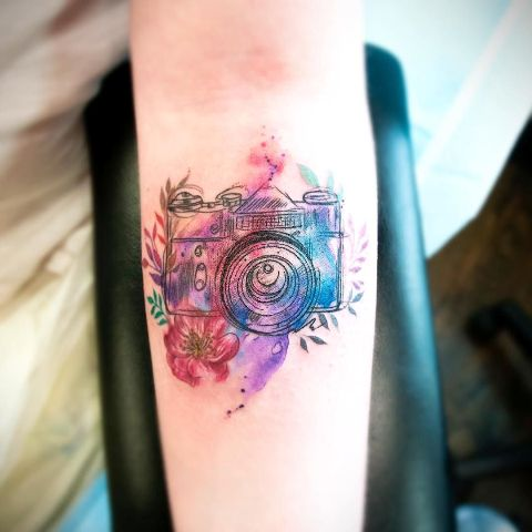 Colorful camera tattoo on the forearm