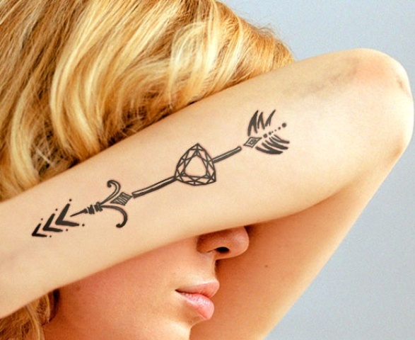 Diamond and arrow tattoo on the forearm