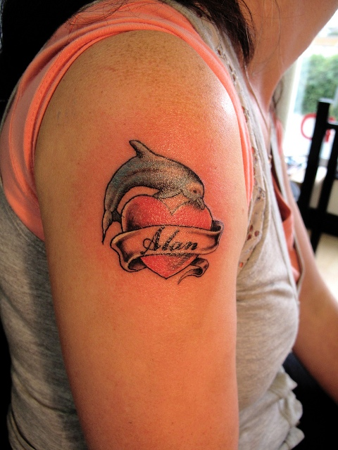Dolphin and heart tattoo on the hand