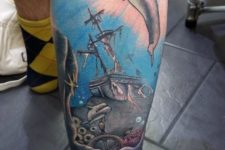 Dolphin and ship tattoo on the leg