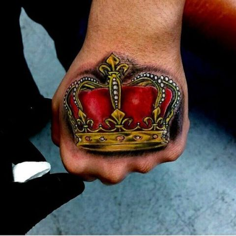 Golden and red crown tattoo on the hand