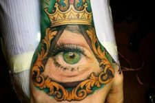 Green eye and crown tattoo on the hand