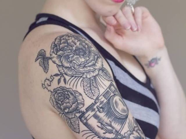 Half-sleeve camera and big flowers tattoo