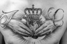 Hands, heart and crown tattoo on the chest