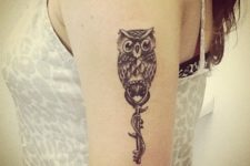 Key and owl tattoo on the arm