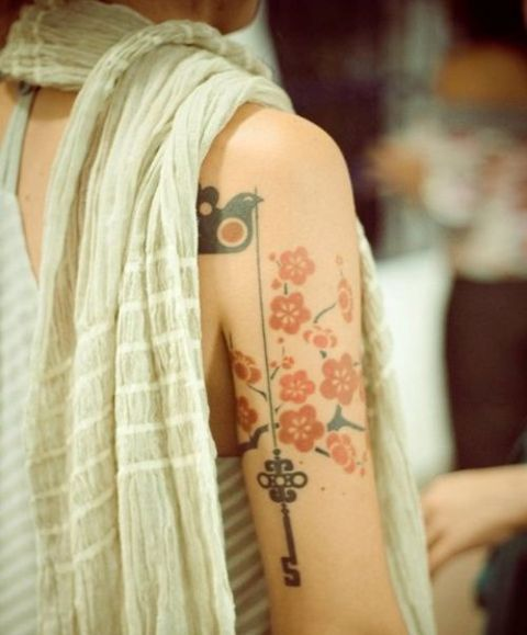 Key, bird and red flowers tattoo on the arm