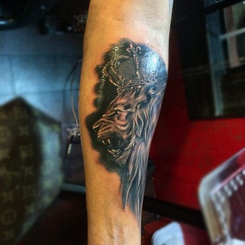 Lion and crown tattoo on the forearm