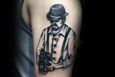 Man with retro camera tattoo on the hand