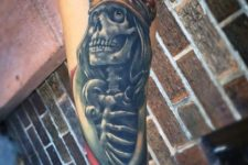 Skeleton and crown tattoo on the forearm