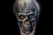 Skull and crown tattoo on the biceps