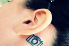 Tiny camera tattoo behind the ear