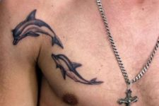 Two dolphin tattoos on the chest and shoulder