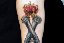 Two gray screws and crown tattoo on the arm