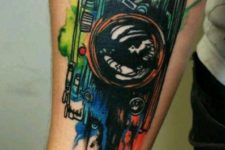 Watercolor camera tattoo on the forearm