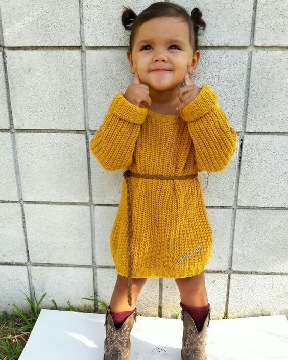 a mustard knit dress with a brown belt, cowboy boots and red socks for a boho feel