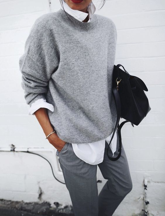 grey pants, a white shirt, a grey sweater and a black bag for any work