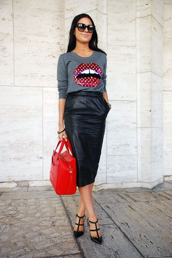 a black leather midi with pockets, black psiked heels, a grey sweatshirt and a red bag