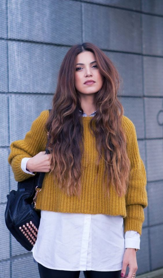 black jeans, a white shirt, a cropped mustard sweater and a spiked bag