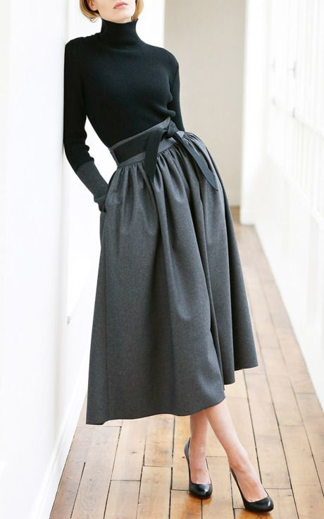 a black turtleneck, black shoes and a grey A line full skirt with pockets