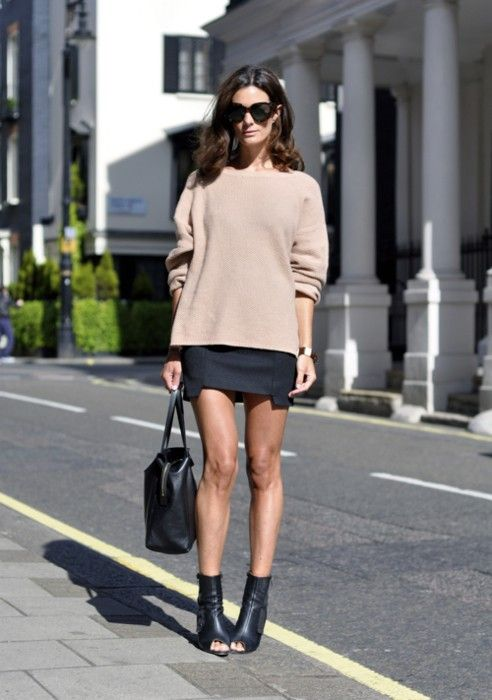 a chunky beige sweater, a black mini skirt, black leather booties and a bag