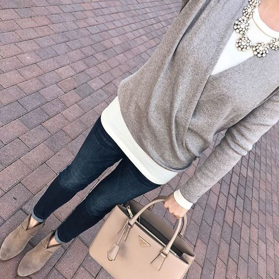 a white long sleeve top, a grey sweater over it, a statement necklace, navy jeans and grey suede booties