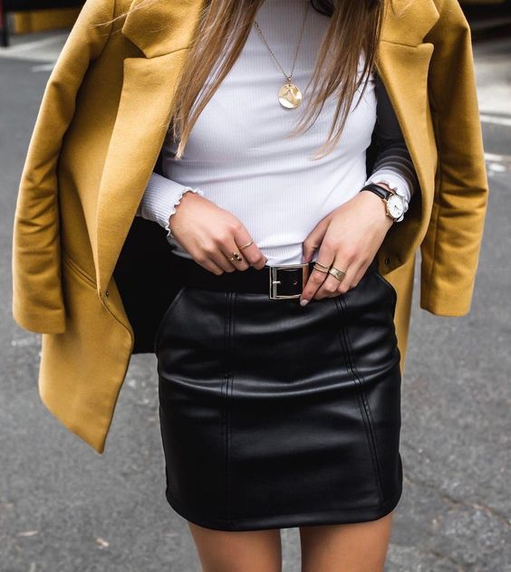a black leather mini skirt, a white turtleneck, a mustard jacket