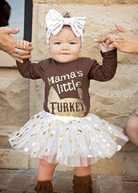 a gold polka dot tutu skirt, a brown printed long sleeve shirt and leather boots