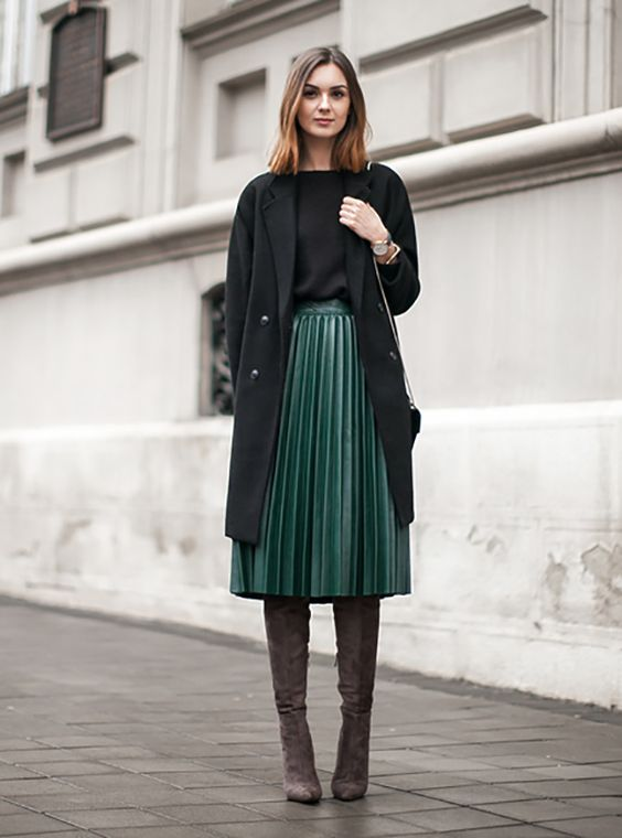 a green midi pleated skirt, a black top, a black coat and brown suede boots