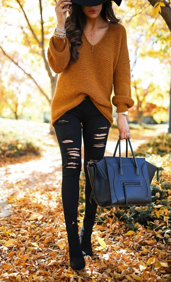 a mustard V-neckline sweater, black ripped denim, black suede boots and a black bag