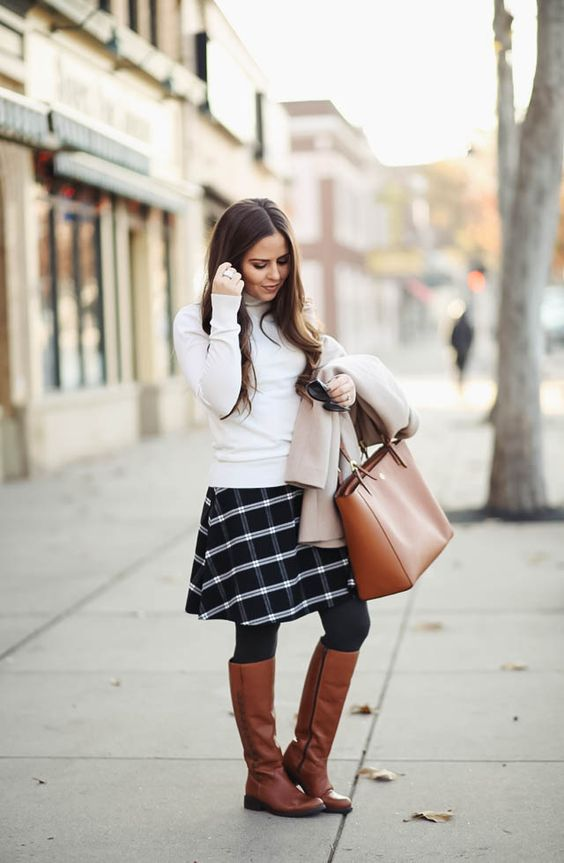 a white turtleneck, a checked black and white skirt, brown rider boots and a matching bag