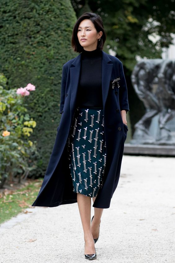 a black turtleneck top, a printed teal knee pencil skirt, black shoes and a navy half sleeve coat