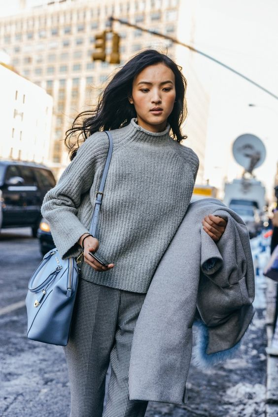 grey gingham pants, a grey sweater and coat plus a blue bag
