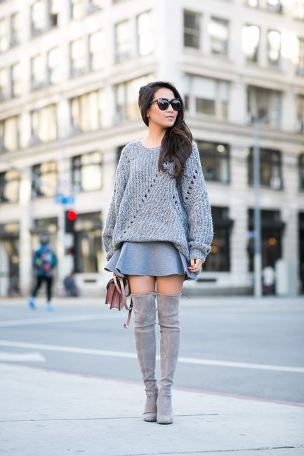 a grey oversized sweater, a grey mini skirt, grey suede tall boots and a brown bag for a transitional look