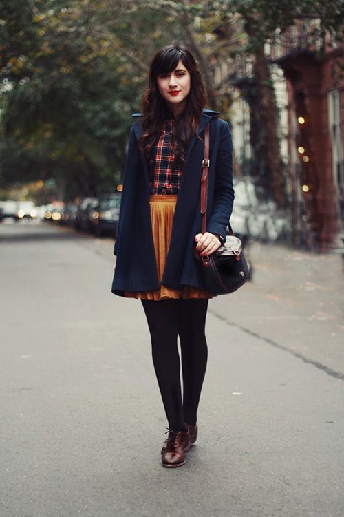 a plaid shirt, a yellow vlvet pleated skirt, black tights and brown vintage shoes, a black coat