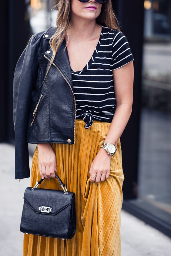 a striped black and white tee, a yellow pleated velvet midi skirt, a black leather jacket and a black bag