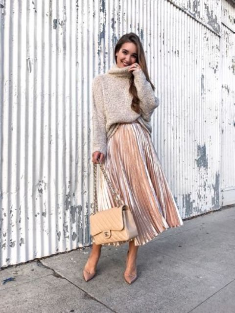 a pink velvet pleated midi skirt, an oversized neutral swetaer, pink shoes and a neutral bag
