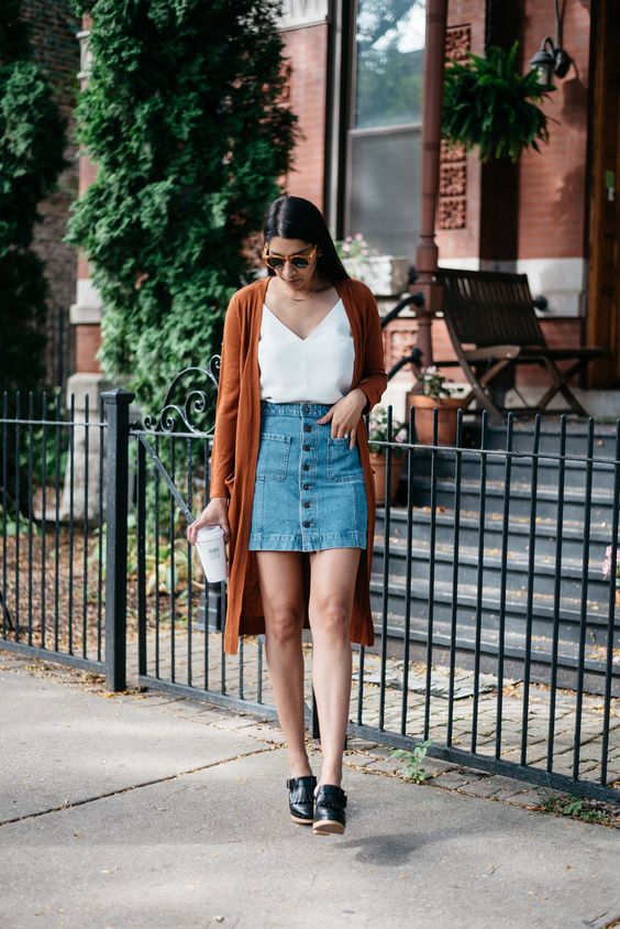a white V-neckline top, a denim skirt with a button row, a long burnt orange cardigan and black leather shoes