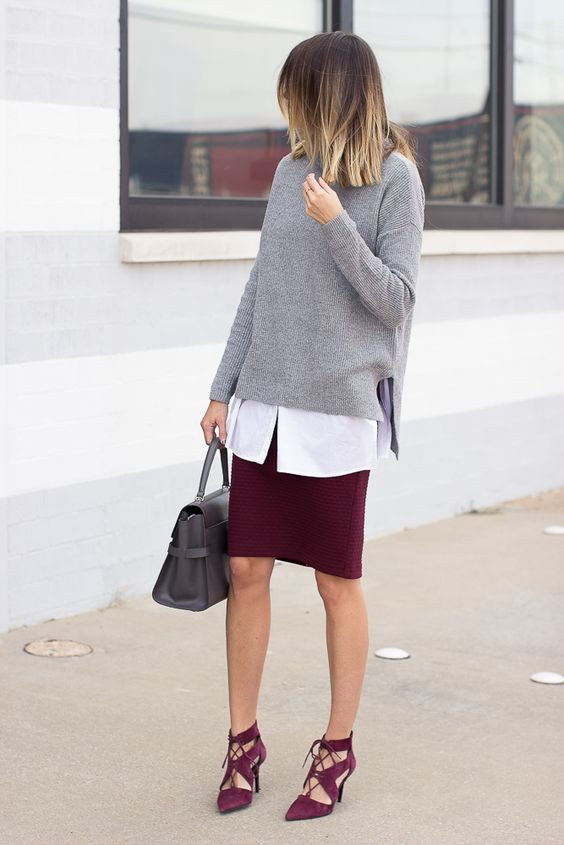 a burgundy skirt and matching strappy shoes, a white shirt, a grey chunky sweater and a grey bag