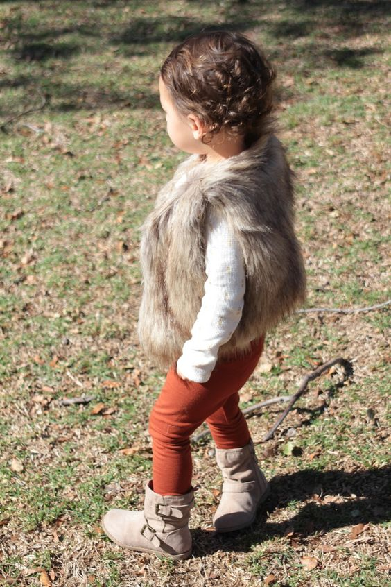 burnt orange pants, a white polka dot sweater, a faux fur vest and beige leather boots