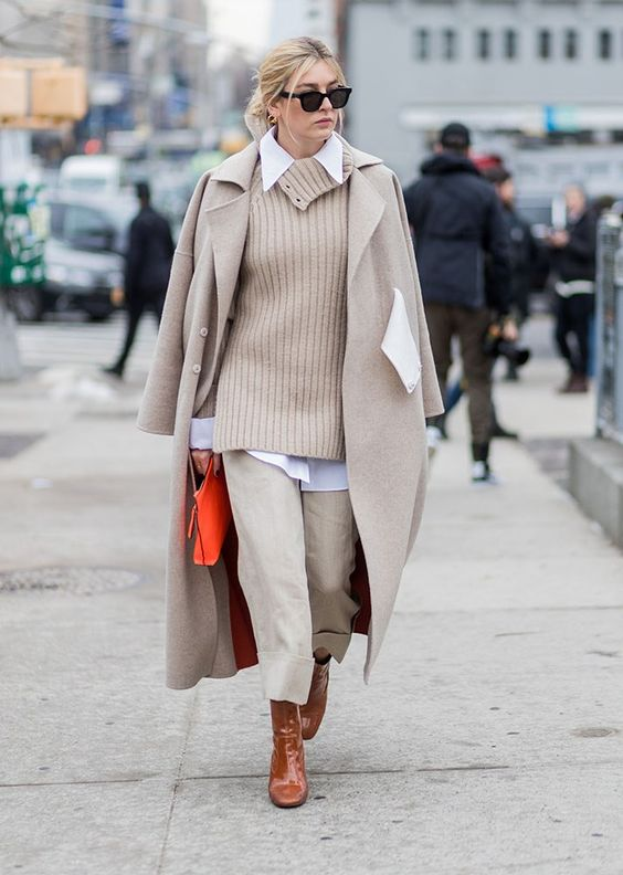 neutral pants, a blush sweater over a white shirt, a neutral coat and brown sock boots