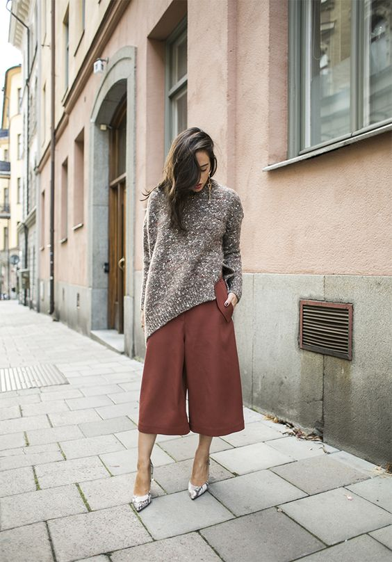 a brown oversized sweater, rust-colored culottes and snake print shoes