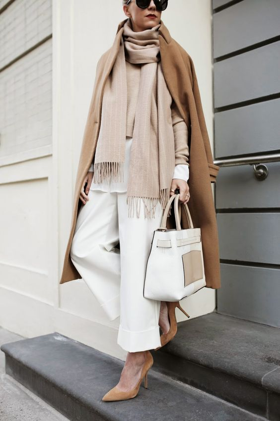 a chic look with a white long sleeve top, white pants, a blush sweater and scarf, a camel coat and shoes